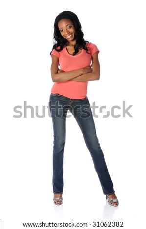 Beautiful African American woman with arms crossed dressed in jeans and high heels - stock photo