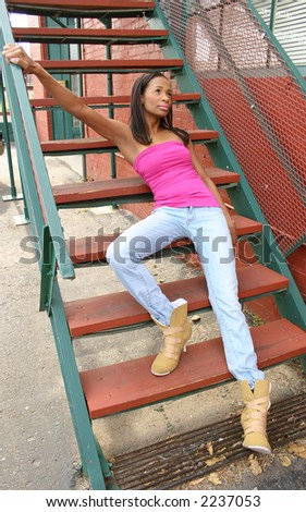 Beautiful African American 21 year old woman sitting on outdoor staircase. - stock photo