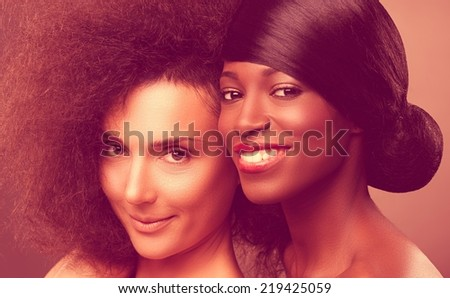 Beautiful african and caucasian women smiling. Caucasian with afro hair. - stock photo