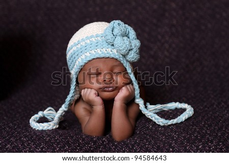 Beautiful African baby resting on her elbows and hands - stock photo