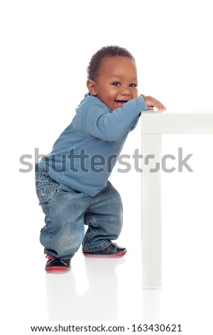 Beautiful african baby standing with a table isolated on a white background - stock photo