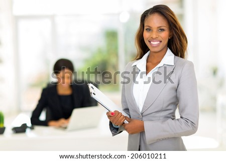 beautiful african businesswoman holding clipboard - stock photo
