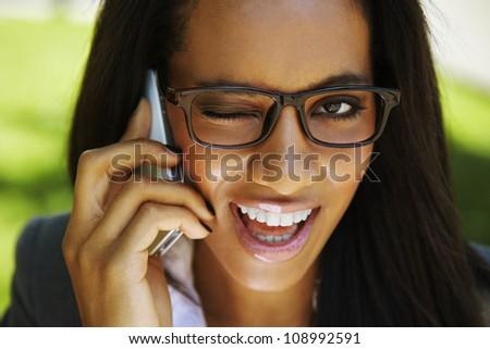 beautiful african businesswoman winking - talking phone - stock photo