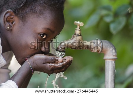Beautiful African Child Drinking from a Tap (Water Scarcity Symbol).  Young African girl drinking clean water from a tap. Water pouring from a tap in the streets of the African city Bamako, Mali. - stock photo