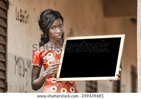 Beautiful African Ethnicity University Girl Holding and Pointing to Blackboard (Schooling Education Symbol) - stock photo