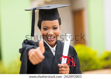 beautiful african female graduate giving thumb up at graduation ceremony - stock photo