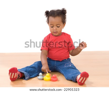 Beautiful african girl playing with three ducks of plastic - stock photo
