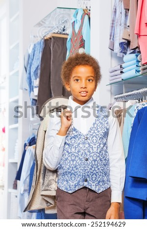 Beautiful African small boy holding jacket in shop