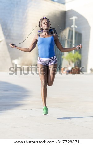 Beautiful african sport woman jumping rope in the street, healthy lifestyle concept. - stock photo