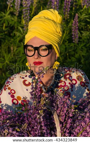 Beautiful african style middle-aged caucasian woman in turban with flowers.