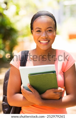 beautiful african university student holding books