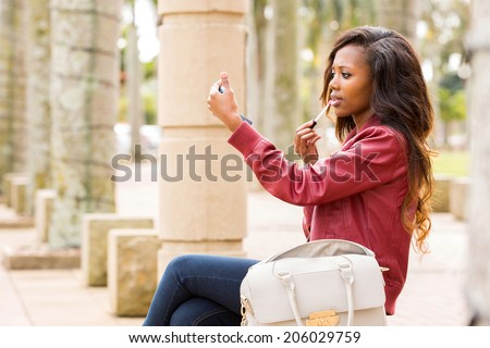 beautiful african woman holding mirror and applying lip gloss - stock photo