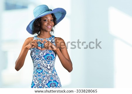 Beautiful african woman making a heart shape with her hands - stock photo