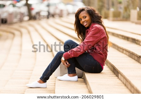 beautiful african woman outdoors sitting on steps - stock photo