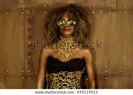 Beautiful African woman posing in fashionable sunglasses and gold necklace on bronze background - stock photo