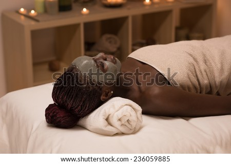 Beautiful african woman relaxing in spa salon with mud mask on face. Beauty treatment therapy - stock photo