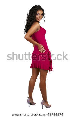 Beautiful African woman with long curly hair in pink party dress on high heels