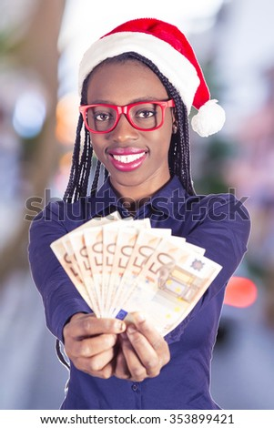 beautiful African woman with money and Christmas hat  - stock photo
