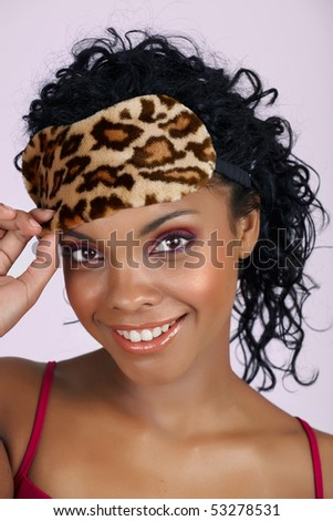 beautiful African woman with natural lips and pink eyeshadows wearing a leopard print sleeping mask over long curly hair - stock photo