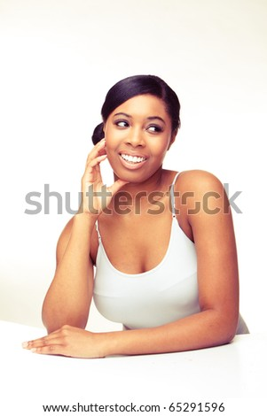 Beautiful African woman with natural make-up laughing on white background.