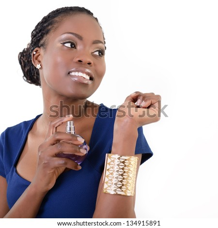 Beautiful african woman with perfume, young cheerful girl holding bottle of perfume and smelling aroma, over white background - stock photo