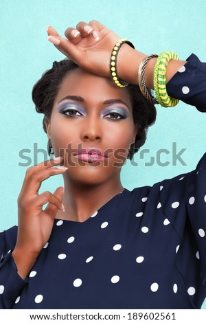 Beautiful African woman with pink lips and eye shadow makeup and jewelry - stock photo
