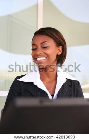 Beautiful African woman working on laptop at office building - stock photo