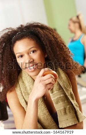 Beautiful afro girl resting at gym, eating apple, smiling. - stock photo