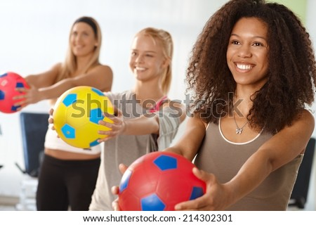 Beautiful afro woman exercising with ball at the gym. - stock photo