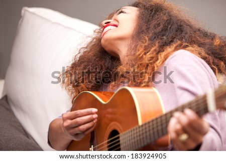 beautiful afroamerican woman on a sofa playing her guitar smiling and throwing out her little tongue in a funny way - stock photo