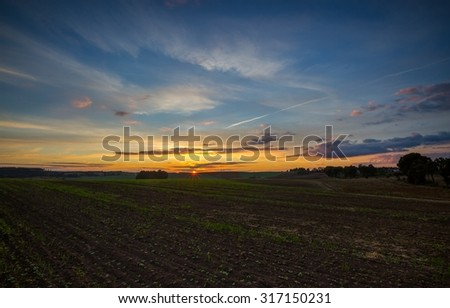 Beautiful after sunset sky over fields. Colorful landscape - stock photo