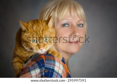 Beautiful aged woman hugging her red cat on grey background. Focus on a cat. - stock photo