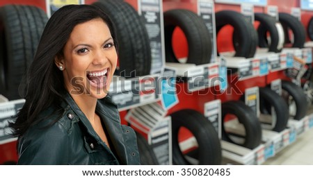 Beautiful agent woman in car repair service over tire background.
