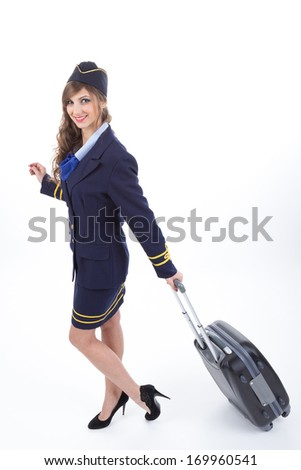 Beautiful air hostess with luggage isolated on white background - stock photo