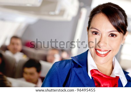 Beautiful air stewardess in an airplane cabin smiling - stock photo