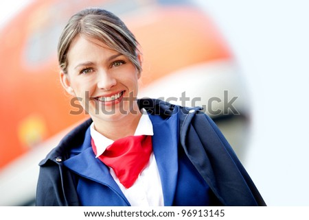 Beautiful air stewardess with a airplane at the background and smiling - stock photo