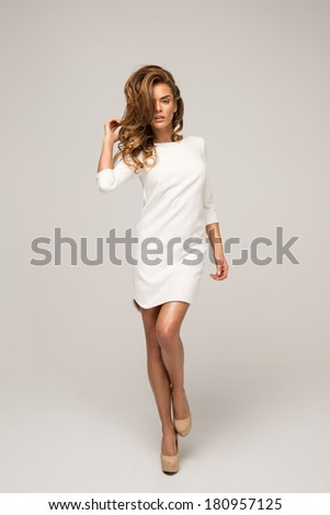 Beautiful alluring woman in white dress - stock photo