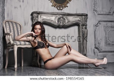 Beautiful alluring young woman in black sexy lingerie posing in antique interior - stock photo