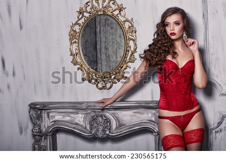 Beautiful alluring young woman in red sexy lingerie posing in antique interior - stock photo