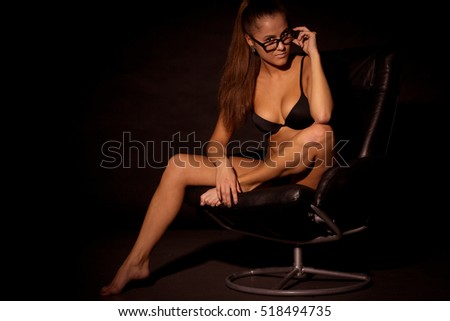 Beautiful alluring young woman in sexy black lingerie at night office.