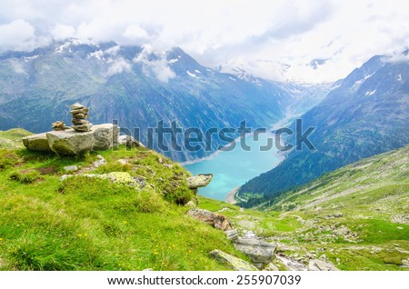 Beautiful alpine landscape with azure lake in the background and trail marking with stones, Zillertal Alps, Austria - stock photo