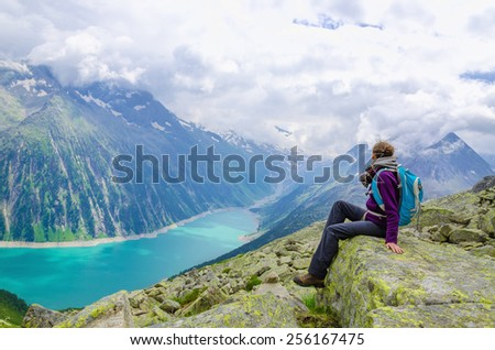 Beautiful alpine landscape with young woman and azure mountain lake in the background, Zillertal Alps, Austria - stock photo