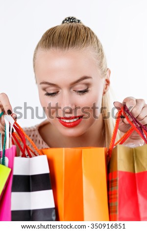 Beautiful amazed blonde woman inspecting content of colored paper bags with fresh buyings. Shopping, consumerism, delivery, present, happy birthday and gifts concept