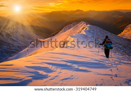 Beautiful amazing sunset winter mountains.  A man goes a sport hike in snow holidays. Christmas background. Unique landscape. Northern country Russia Caucasus. - stock photo