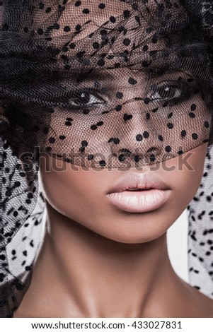 Beautiful american african girl posing. Woman with brown hair, black hat, dark skin. Attractive, sexy fashion model. Fashion shot in studio, on white background. Posing, make up, beauty, grid, veil. - stock photo