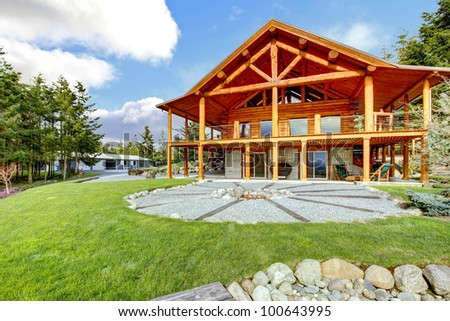 Beautiful American classic log cabin with porch and circle fire pit. - stock photo
