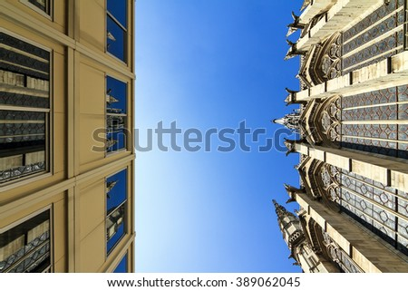 Beautiful ancient church next to a ugly modern building in Paris - stock photo