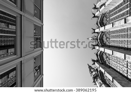 Beautiful ancient church next to a ugly modern building in Paris in BW - stock photo