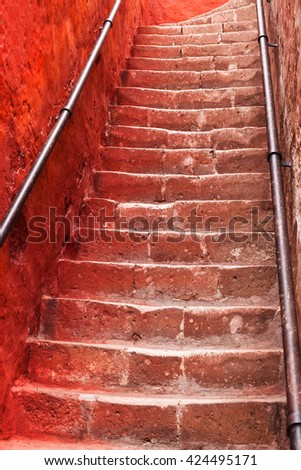 beautiful ancient staircase and red wall - stock photo