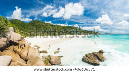 Beautiful and a famous beach Anse Petite seen from the granite boulders, La Digue island, Seychelles. Panorama - stock photo